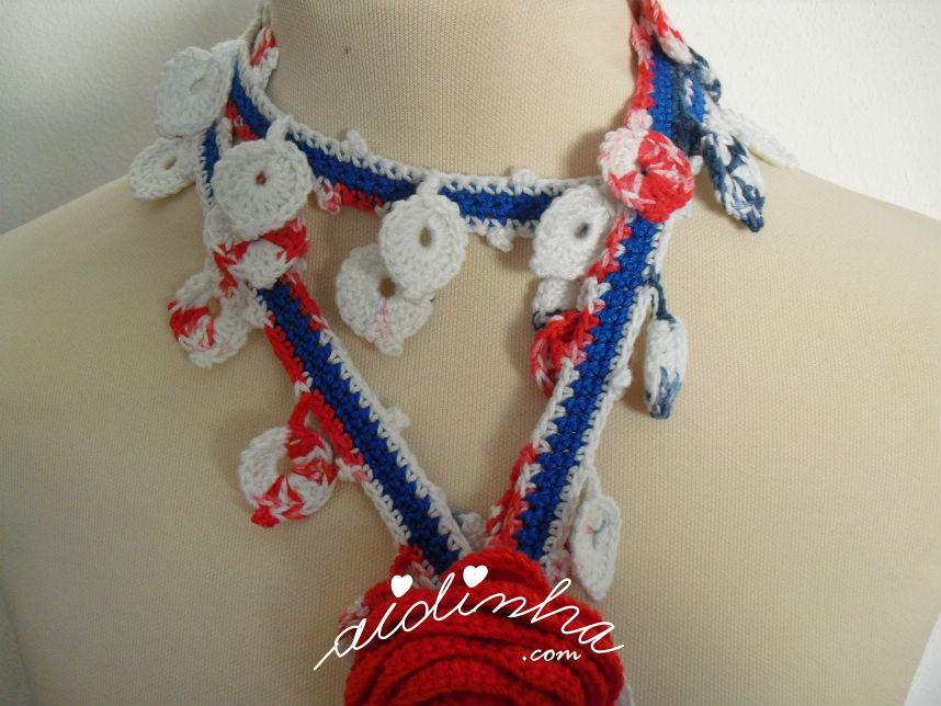 Vista mais de perto, das folhinhas do cachecolar, de crochet, com flor vermelha