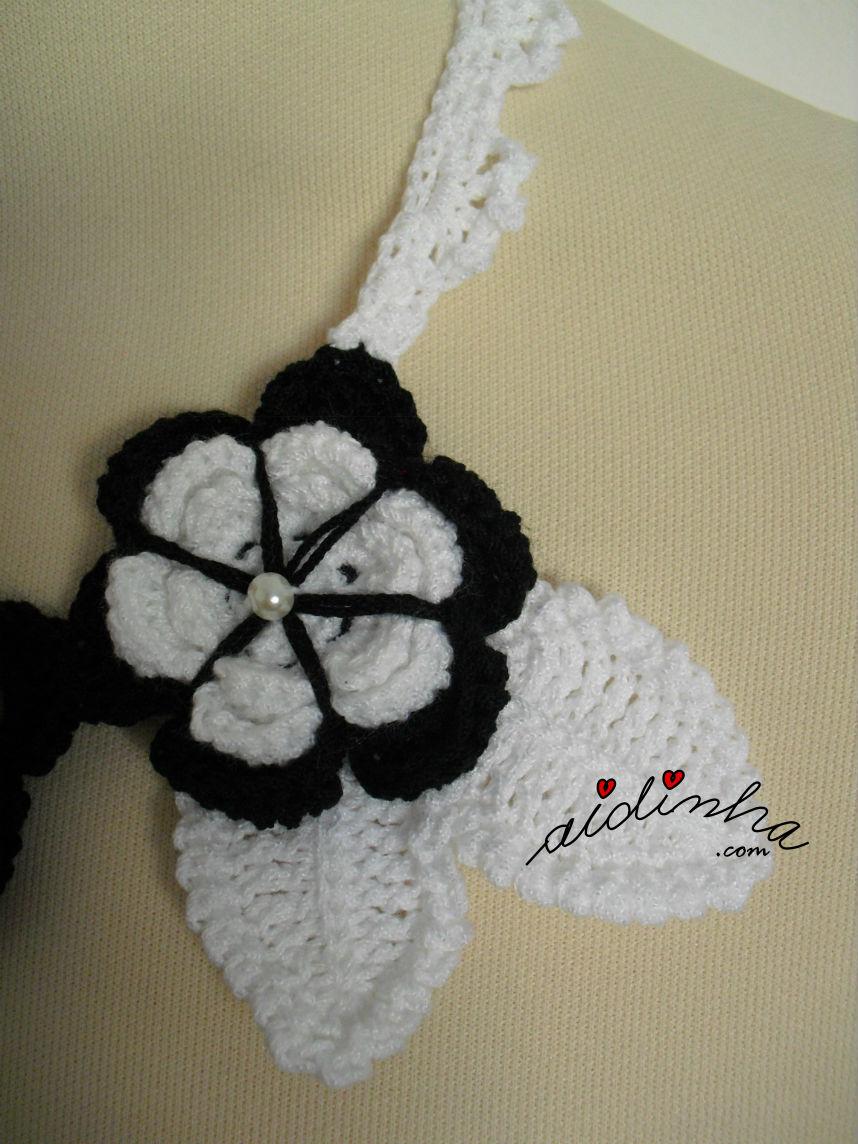 Foto aproximada da flor e das folhas, que compõem o colar de crochet, a preto e branco
