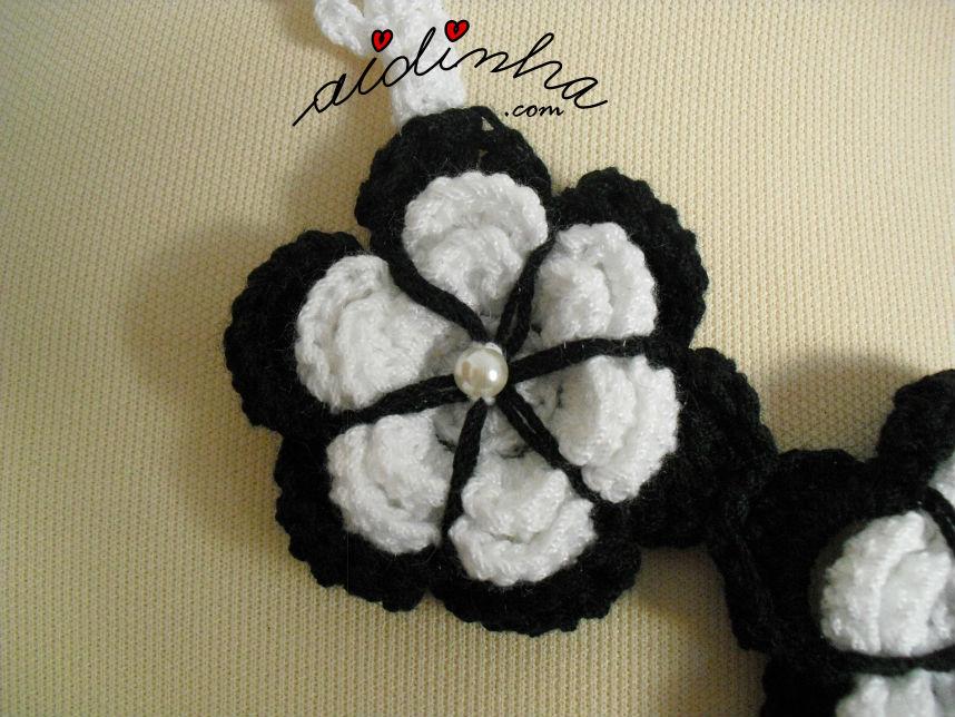 Foto em pormenor da flor do colar, em crochet, a preto e branco