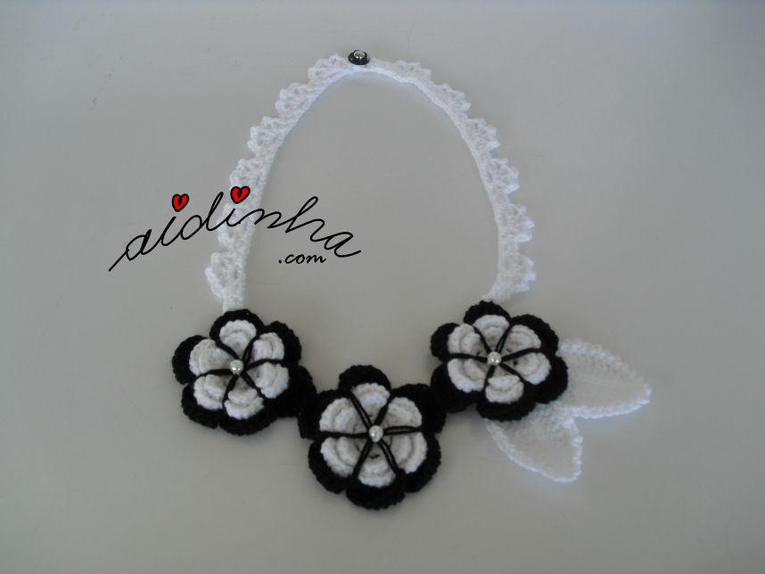 Foto geral do colar, em crochet, com flores a preto e branco
