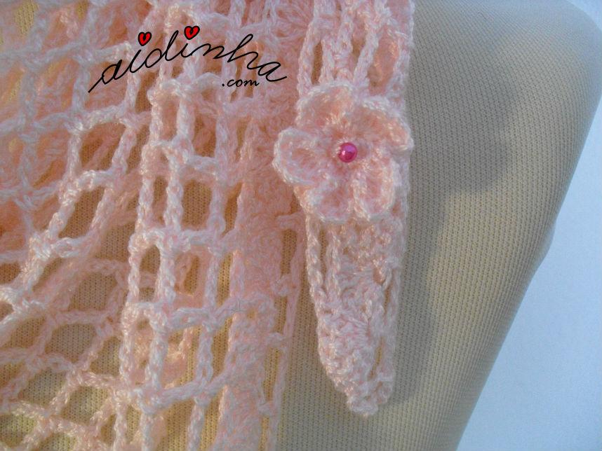 Foto aproximada da florinha aplicada no baktu rosa claro, de crochet
