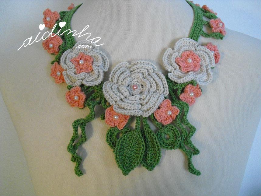 Vista aproximada do colar de crochet, com flores creme e salmão