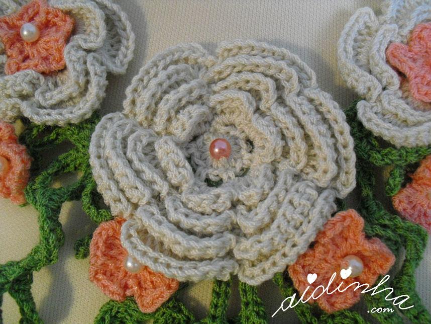 Vista da flor central do colar de crochet, creme e salmão