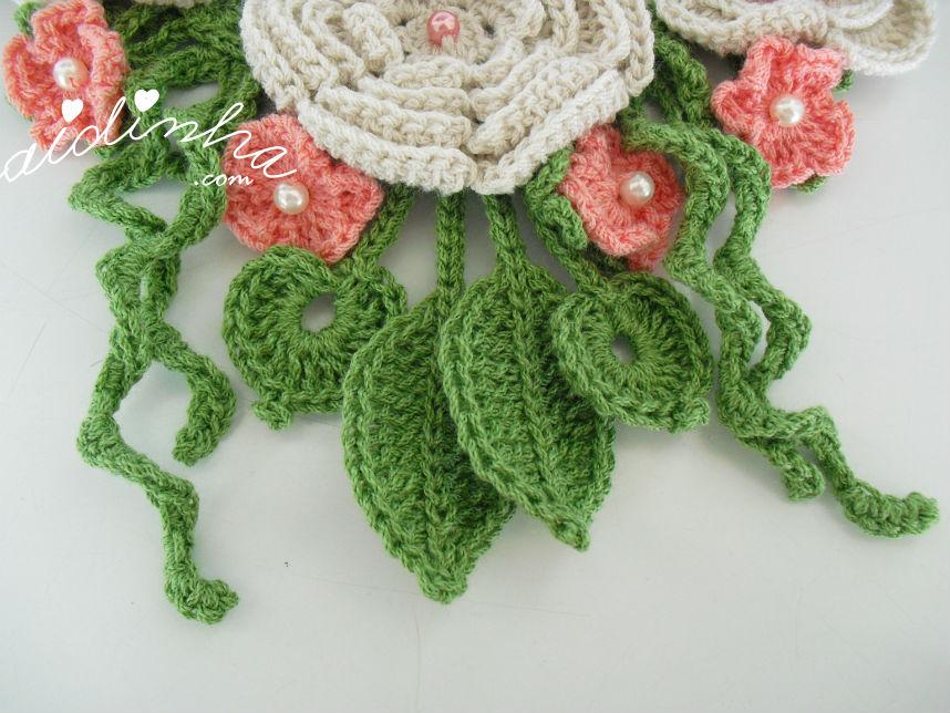 Vista das folhas e enrolados do colar de crochet, creme e salmão