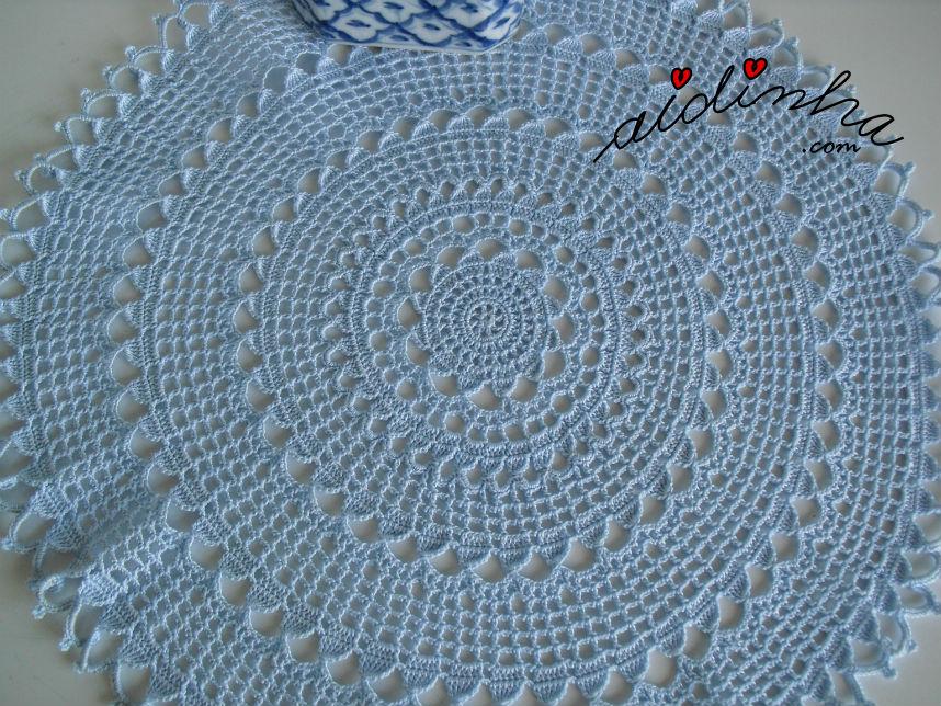 Vista mais aproximada do naperon/caminho de mesa redondo, em crochet, azul