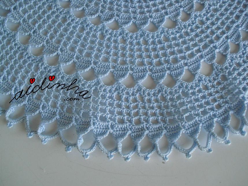 Vista dos arcos do naperon/caminho de mesa redondo, em crochet, azul