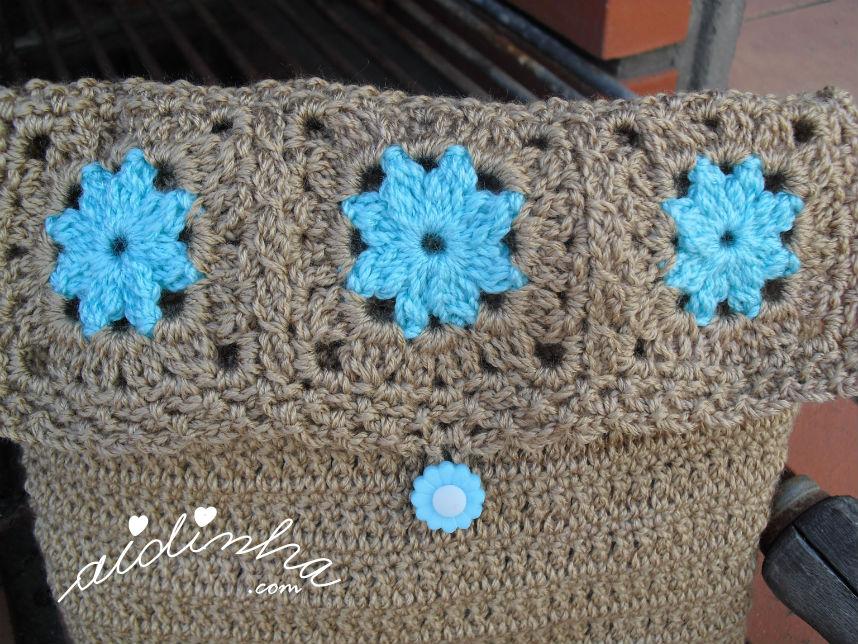Pormenor das rosetas da tampa, da bolsa castanha, de crochet