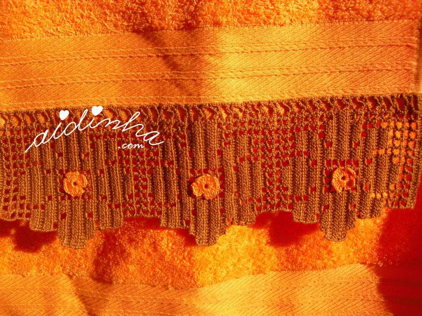 Vista da renda de crochet castanha com florinhas laranja