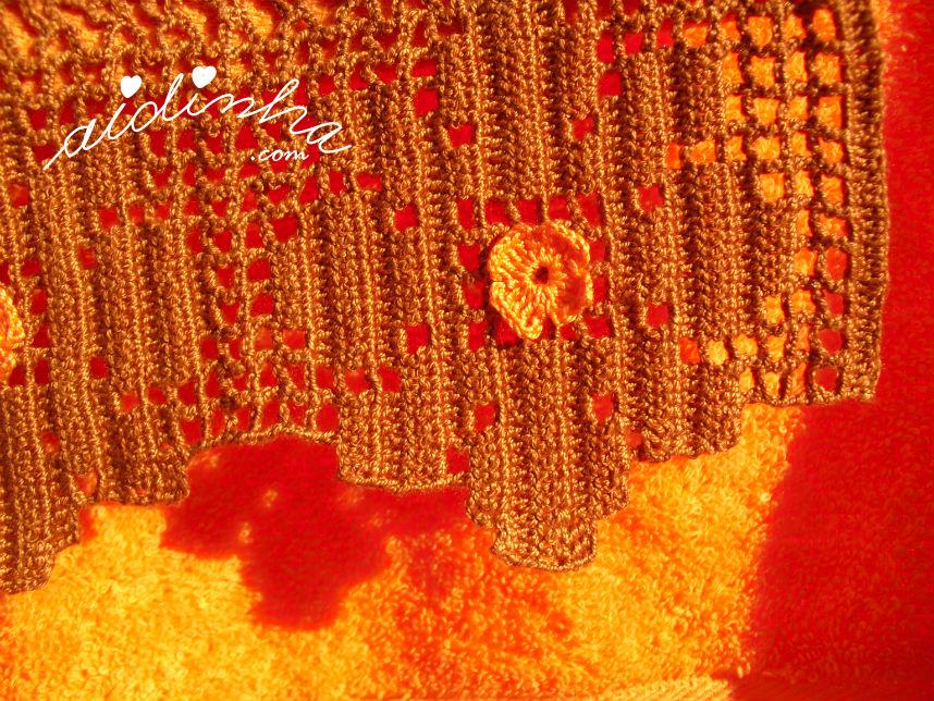 Pormenor da florinha laranja, da renda de crochet castanha
