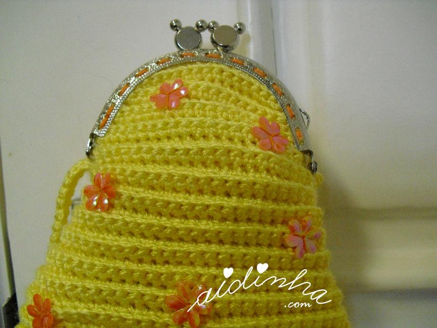Vista mais aproximada da bolsa infantil, em crochet, amarela com florinhas laranja