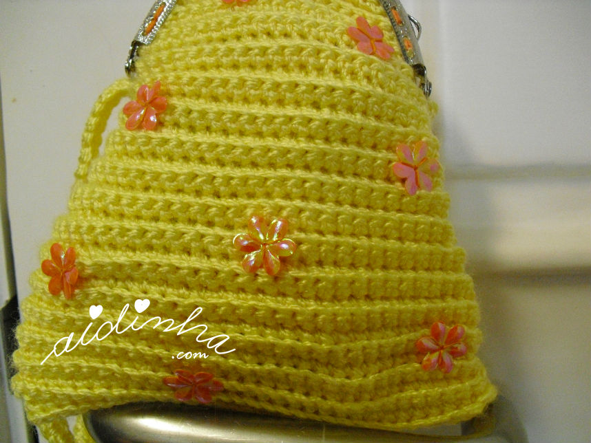 Vista das florinhas laranja da bolsa infantil, de crochet