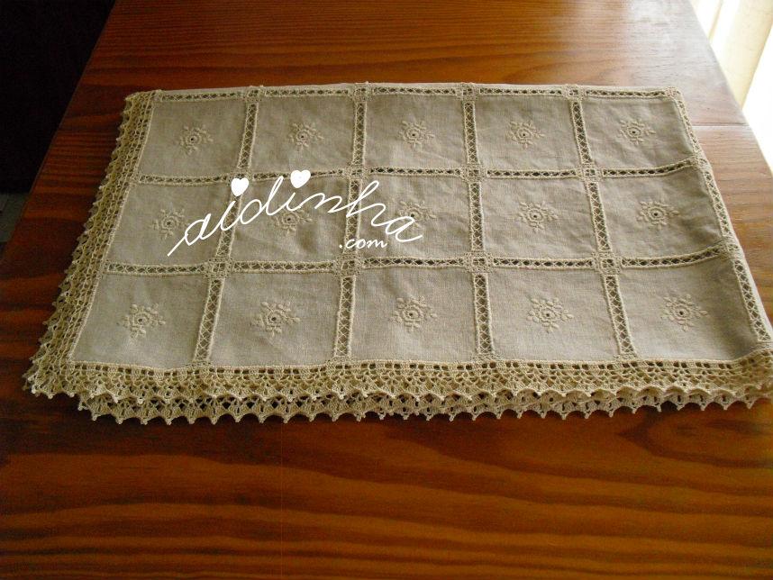 Vista mais aproximada da toalha de linho bordada, com o picô de crochet