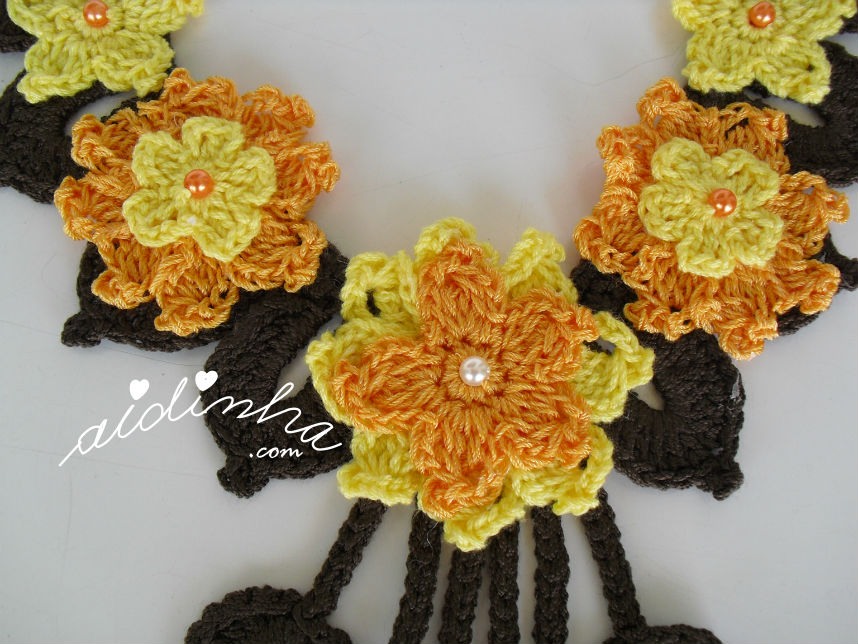 As flores centrais do colar, de crochet, amarelo e laranja