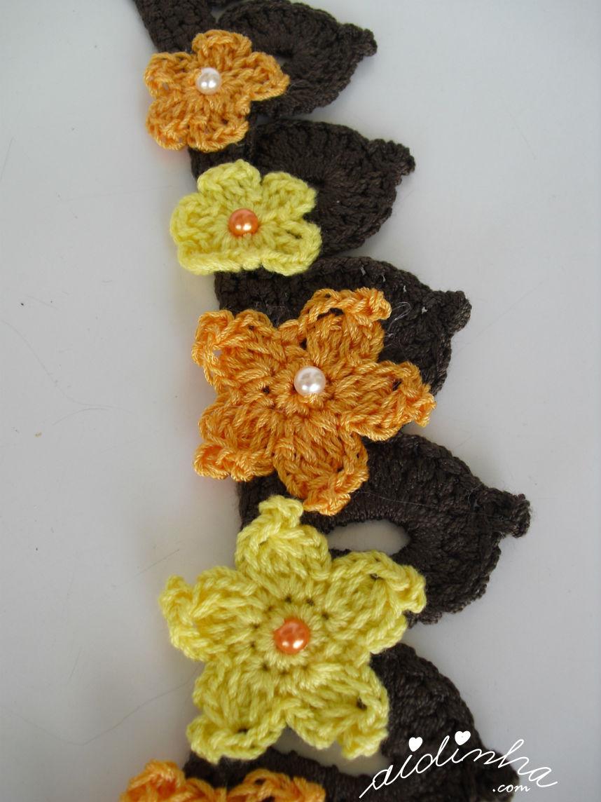 Pormenor das flores laterais do colar de crochet laranja e amarelo