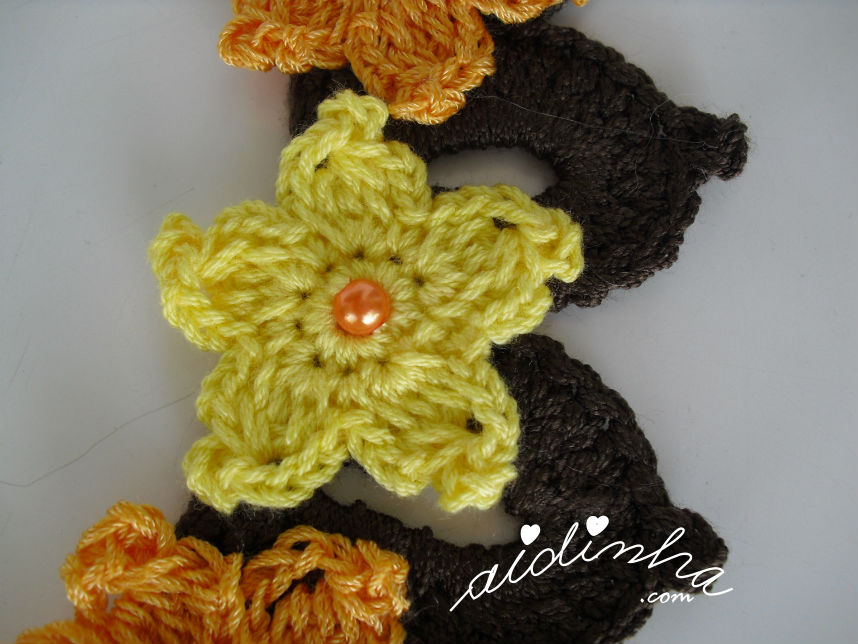 Pormenor da flor estrela amarela do colar de crochet