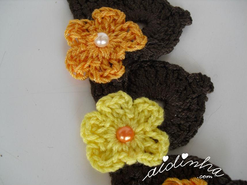 Pormenor das flores pequeninas do colar de crochet amarelo e laranja