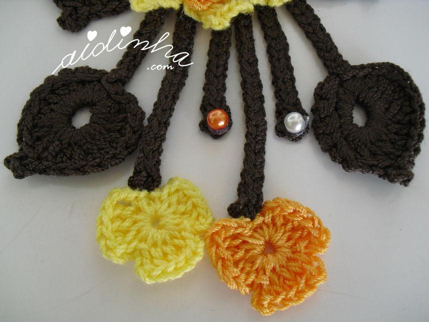 Pormenor dos penduricalhos do colar de crochet amarelo e laranja