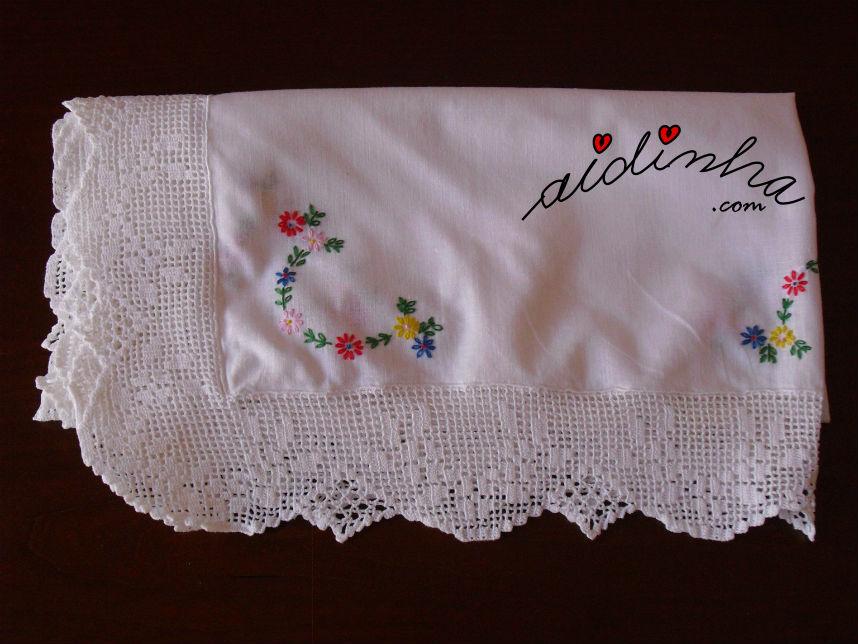 Vista de um dos lados da toalhinha bordada à mão, com renda de crochet