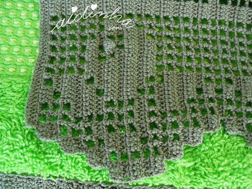 Vista de perto da flor da renda de crochet, das toalhas banho verdes