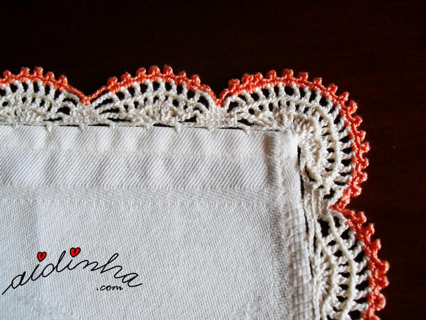 Vista do canto do picô de crochet, creme e laranja da toalhinha mesa