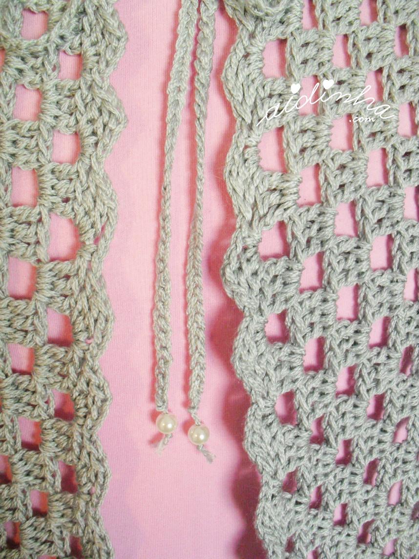 Foto dos cordões, com pérolas, do casaco de crochet cinzento