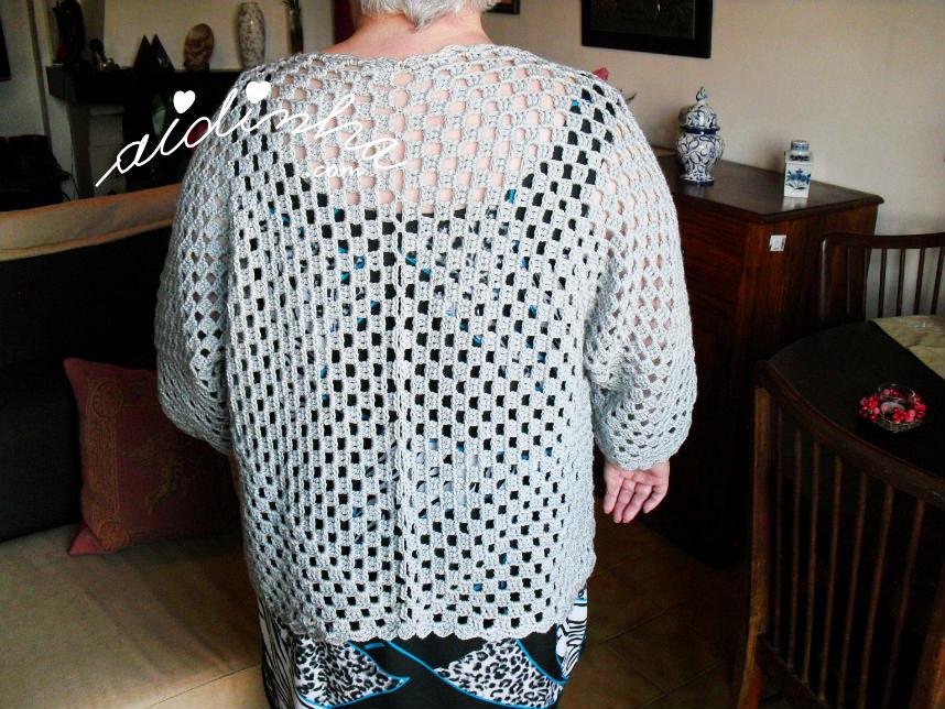 O casaco de crochet, vestido e visto por trás