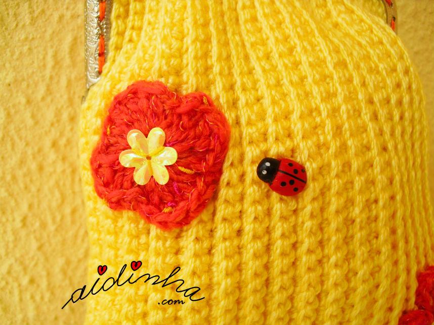 Imagem da flor e joaninha, que enfeitam a bolsa de crochet amarela