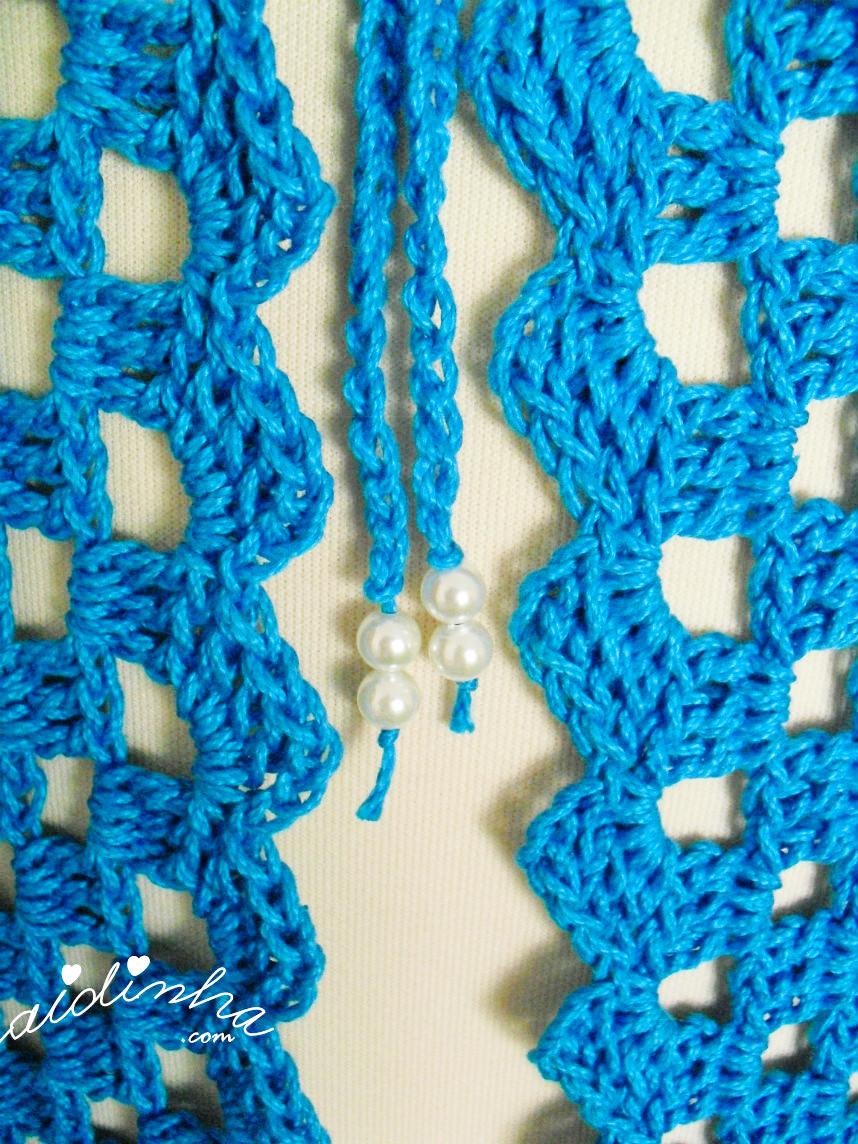Imagem dos cordões com pérolas, do casaco de crochet turquesa