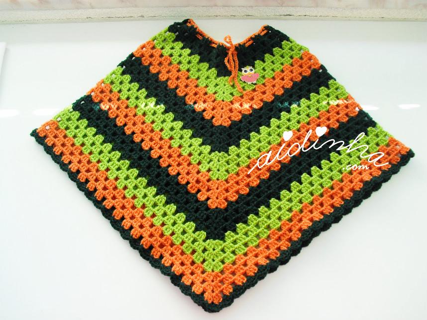 Vista total do poncho infantil, verde e laranja