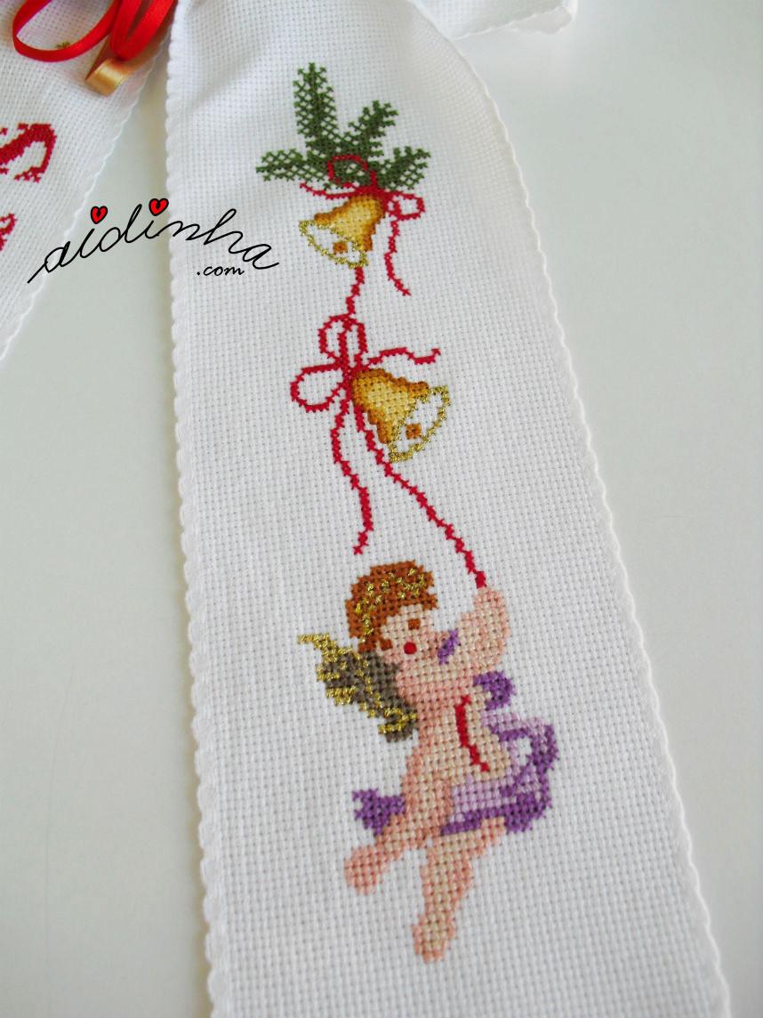 Desenho de anjo, bordado em ponto cruz de um dos lados do laço