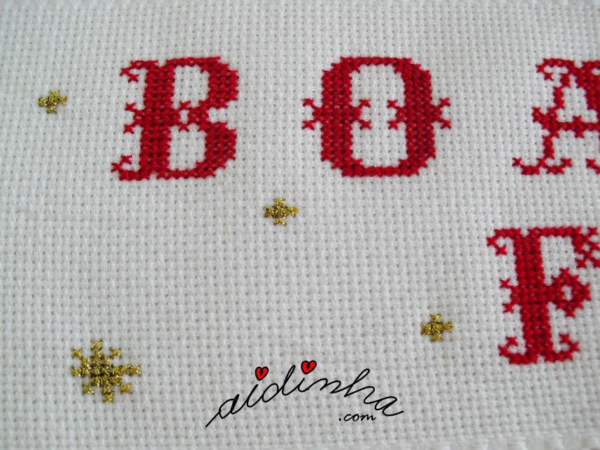 Pormenor das letras bordadas no laço de Natal