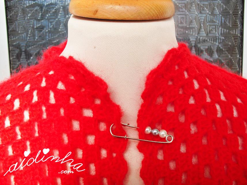 Imagem do alfinete que fecha o casaco de crochet vermelho