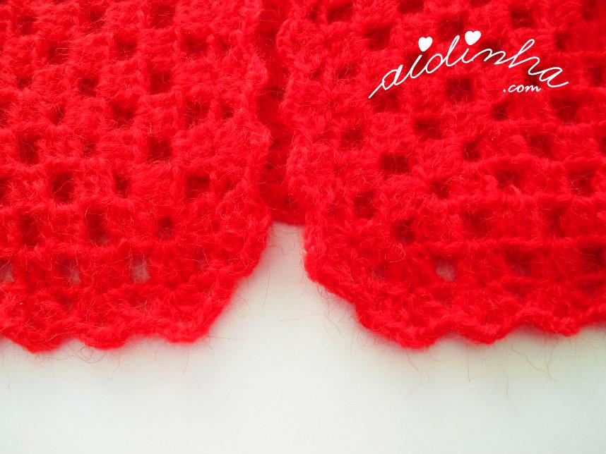Vista dos dois cantos da parte da frente do casaco de crochet vermelho