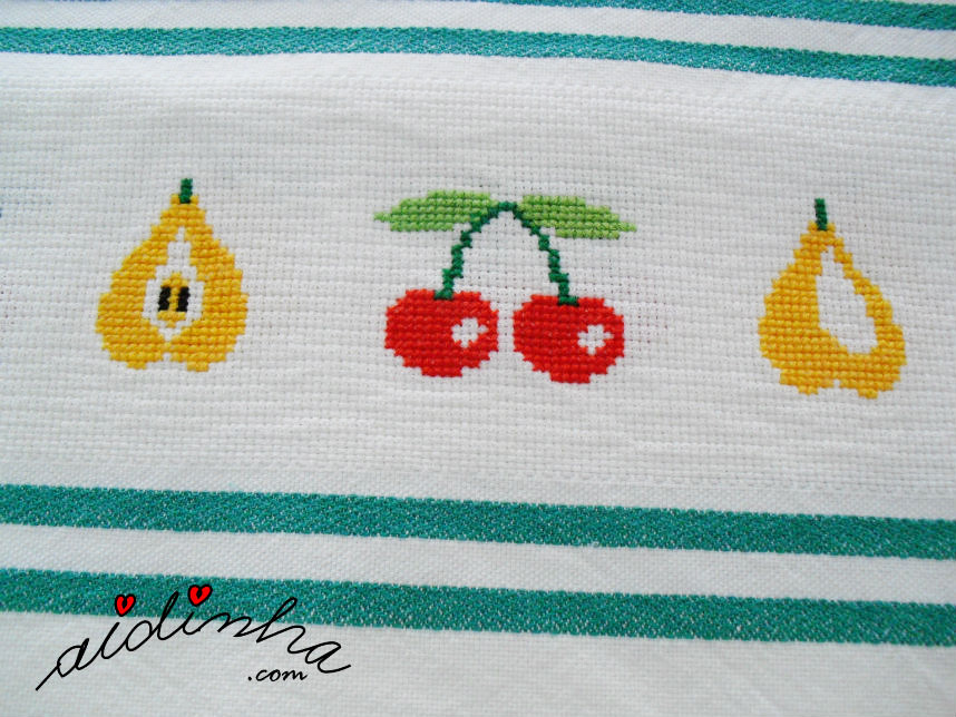 Visto de perto, os desenhos de frutas, bordados em ponto cruz