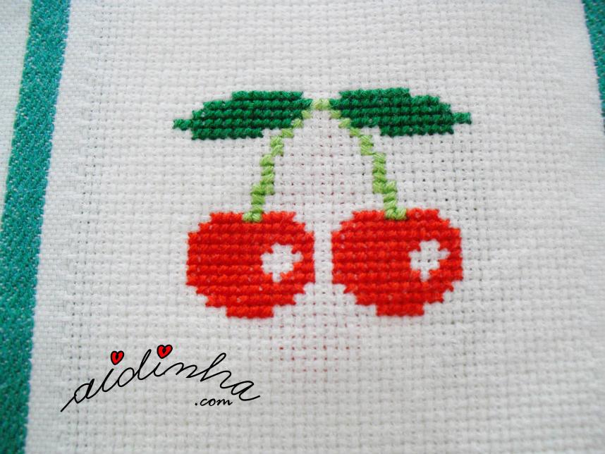 Ramo de cerejas, bordado a ponto cruz, na toalha de mesa