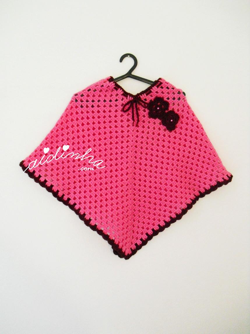Imagem do poncho infantil, em crochet, rosa fuscia e bordeaux, pendurado