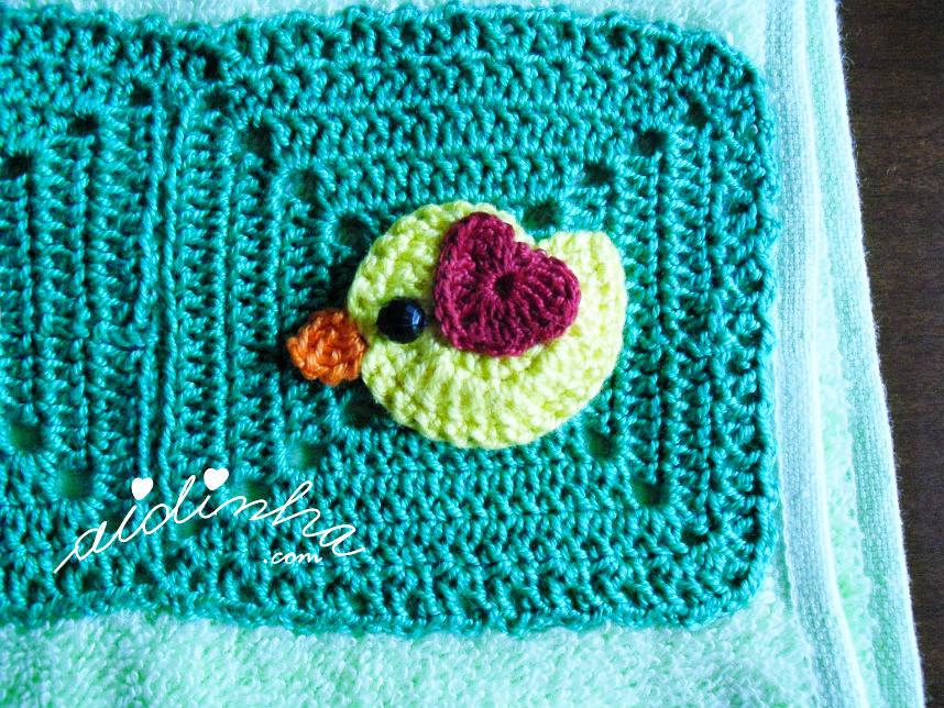 Foto do passarinho verde claro, com asinha bordeaux, de crochet