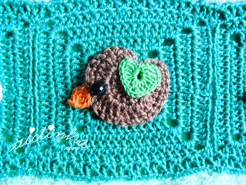 Foto do passarinho castanho escuro, com asinha verde, de crochet