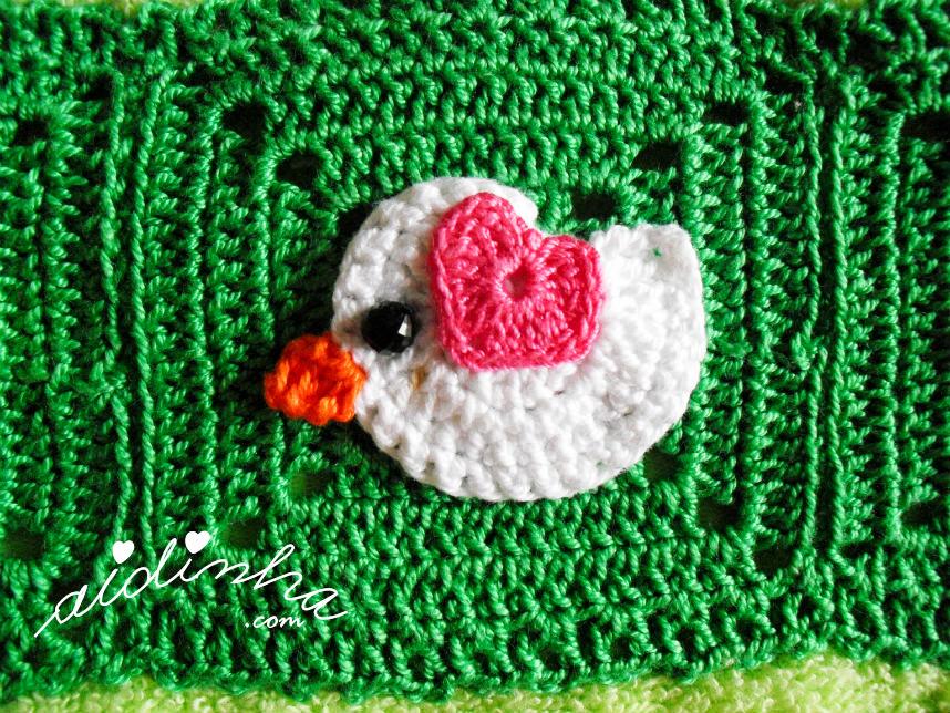 Foto do passarinho branco, com asinha rosa fuscia, de crochet