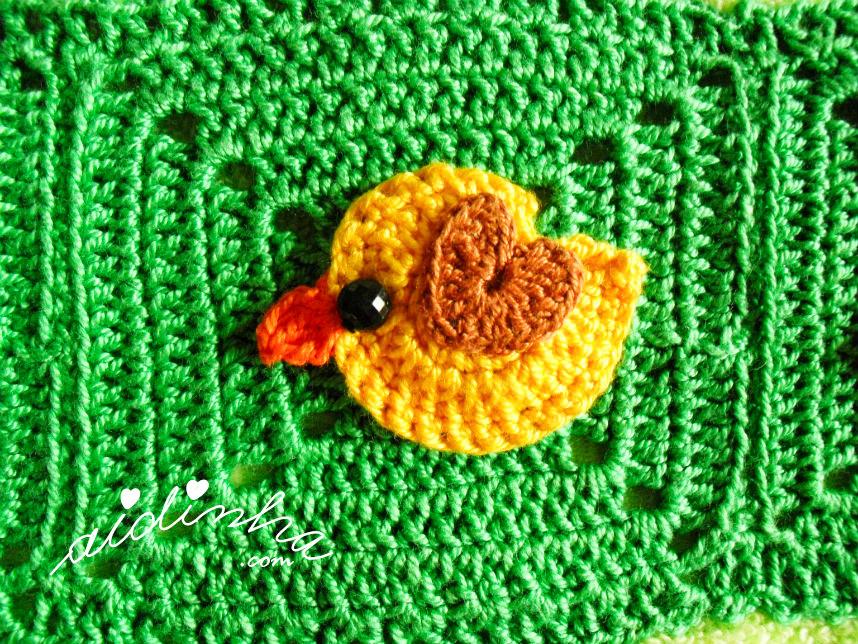 Foto do passarinho amarelo, com asinha castanha, de crochet