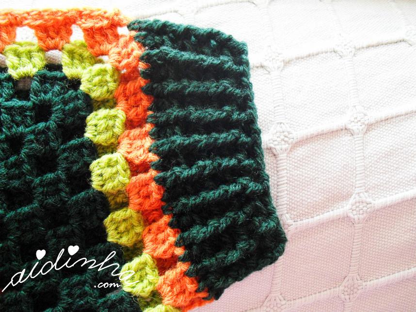 Foto do punho, do casaco infantil, verde e laranja