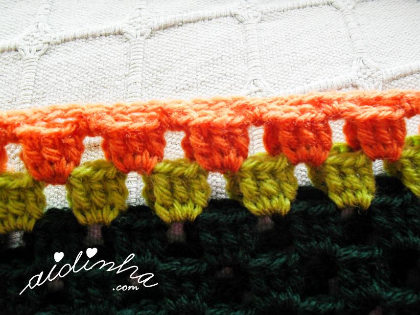 Foto do pegamento dos ombros do casaco infantil, verde e laranja