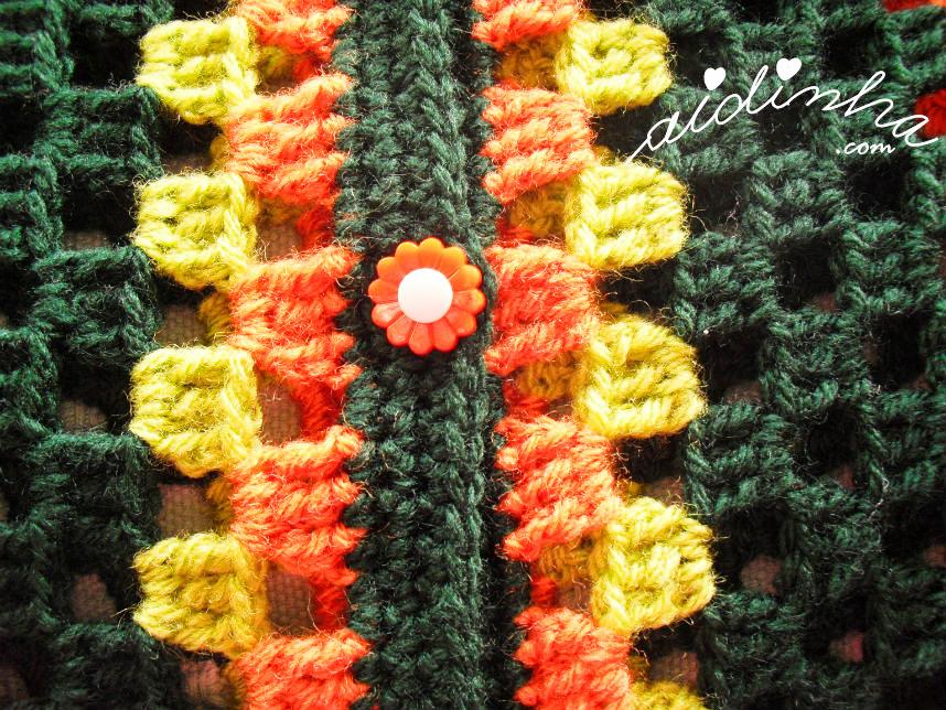 Foto do botão, em forma de flor, laranja do casaco infantil