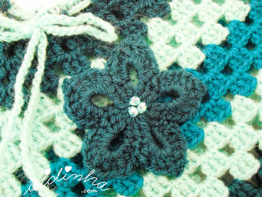 Foto da flor de crochet, que enfeita o poncho turquesa