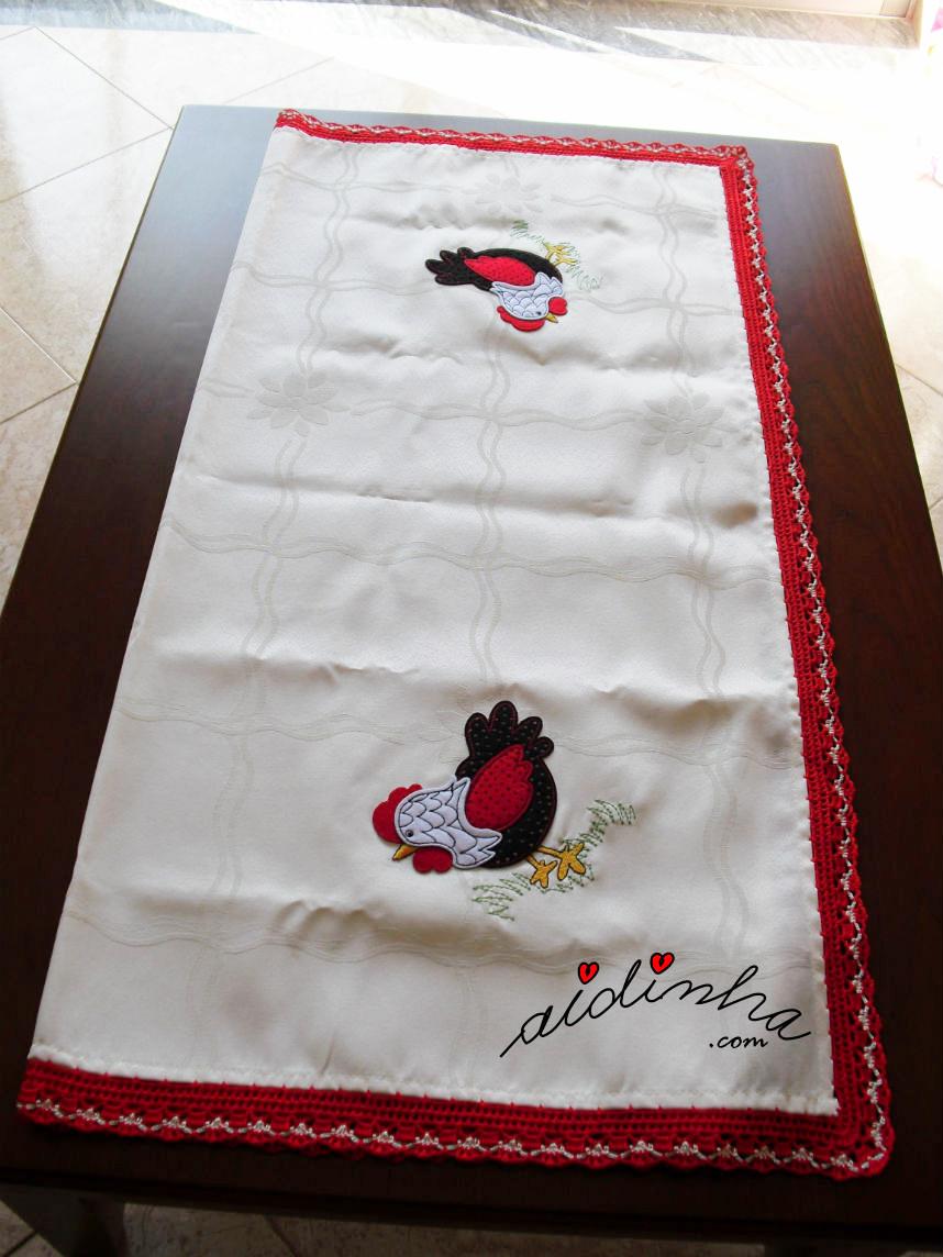 Vista da toalha de mesa, com picô de crochet vermelho e creme