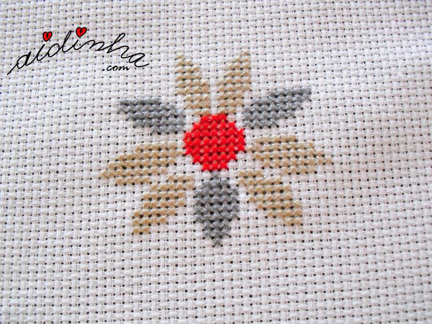 Flor com o centro vermelho e as pétalas creme e cinza