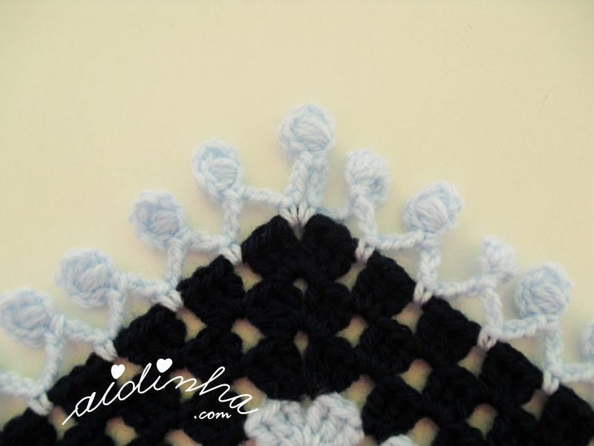 Foto dos pufs no bico do poncho de crochet