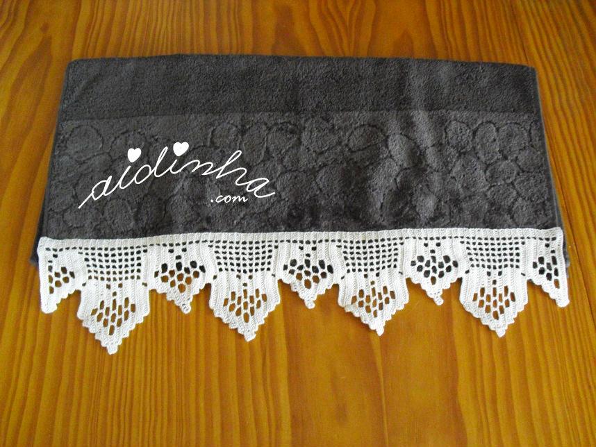 Foto da toalha de rosto castanha, com barra de crochet