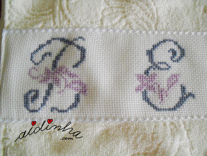 Foto, de perto, das letras em ponto cruz da toalha de banho