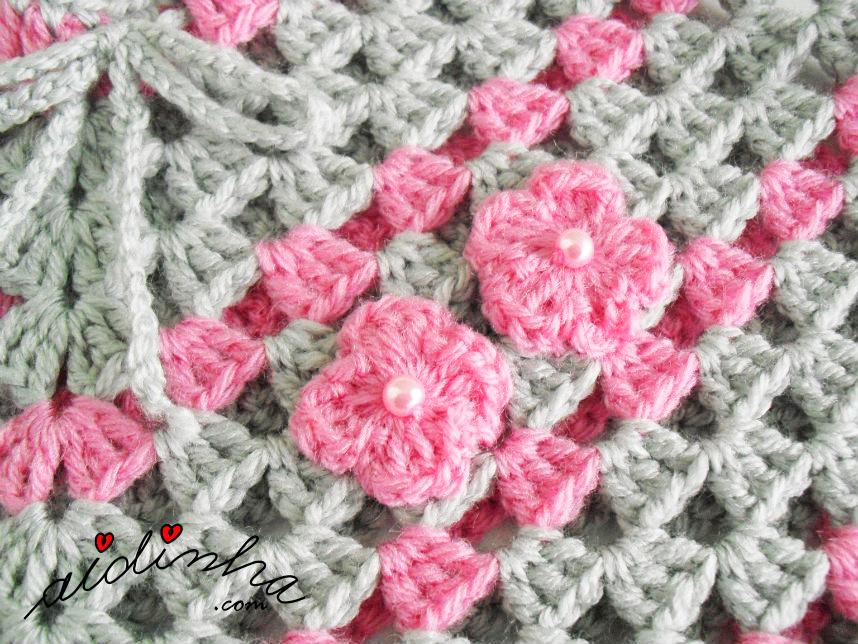 Pormenor das flores de crochet, do poncho rosa e cinza